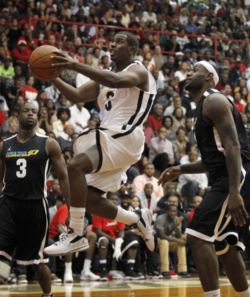 Chris Paul (3) gets past Dwyane Wade, left, and LeBron James on his way to score during the Chris Paul All Star Pick-Up basketball game between NBA players in Winston-Salem, N.C., Saturday, Oct., 1, 2011. The White team won 175-146. (AP Photo/Bob Leverone)