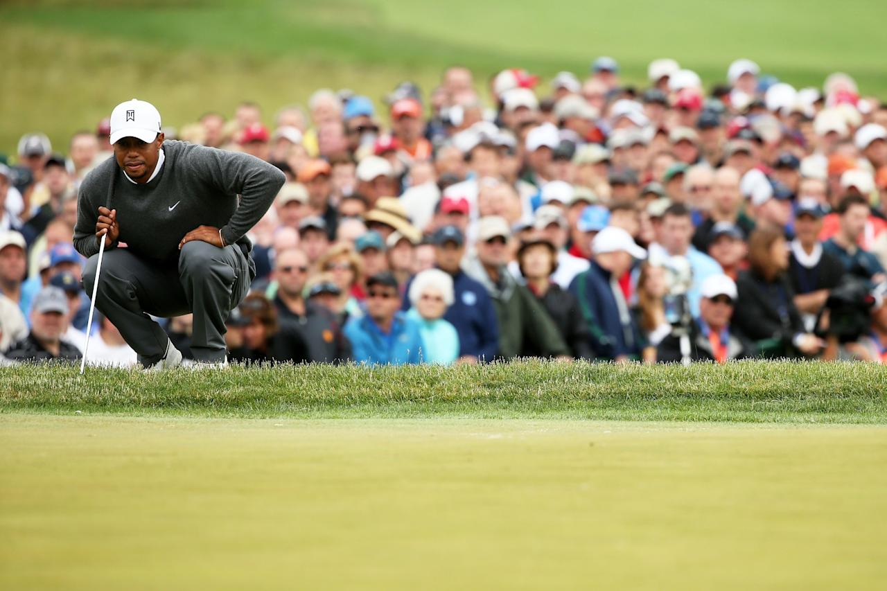 ARDMORE, PA - JUNE 14: Tiger Woods of the United States lines up his putt on the 18th green as a gallery of patrons look on during a continuation of Round One of the 113th U.S. Open at Merion Golf Club on June 14, 2013 in Ardmore, Pennsylvania. (Photo by Andrew Redington/Getty Images)