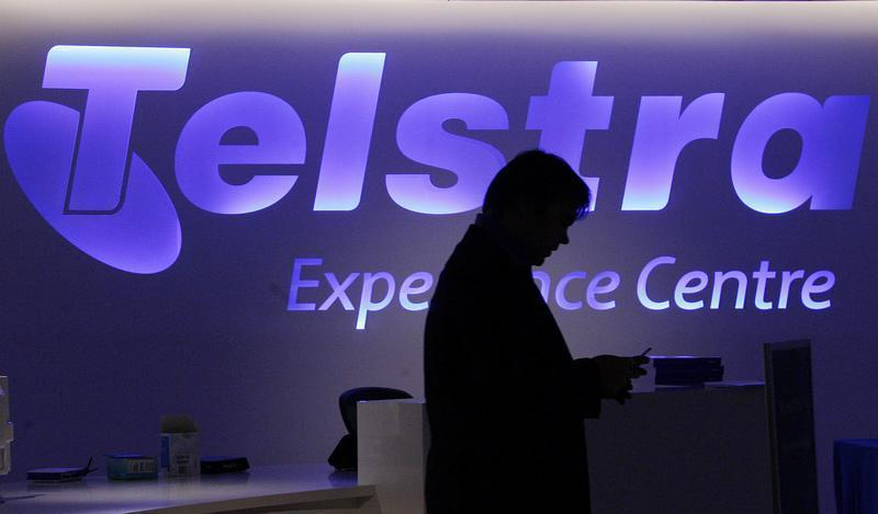 A man uses his mobile phone in front of a Telstra logo in central Sydney
