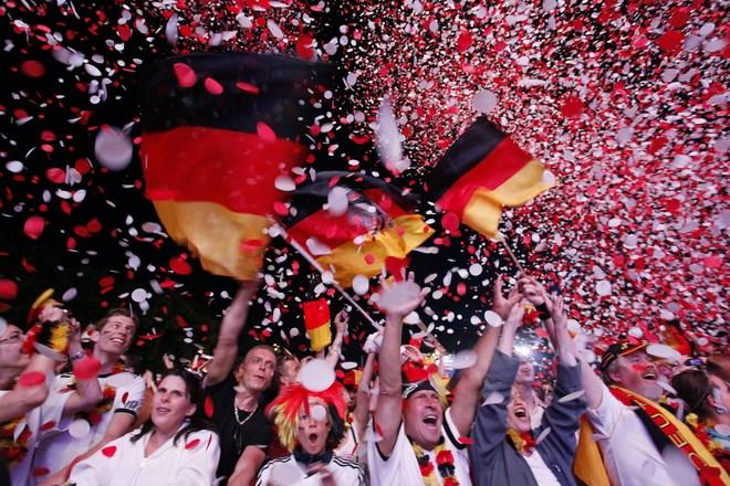 "Supporters of the German national football team cheer with German flags at the end of the public screening of Germany's opening match in the UEFA Euro 2012 against Portugal at the ""Fanmeile"" (Fan Mile) in Berlin on June 9, 2012.  Germany won 1:0 against Portugal. AFP PHOTO / MICHELE TANTUSSIMICHELE TANTUSSI/AFP/GettyImages"