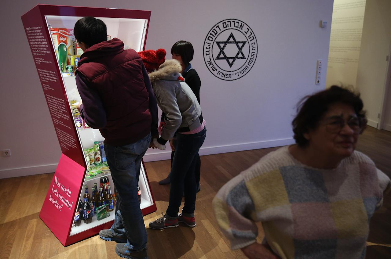 """BERLIN, GERMANY - APRIL 04:  Visitors look at an exhibit of kosher food at the exhibition """"The Whole Truth - Everything You Always Wanted To Know About Jews . . . """" at the Juedisches Museum (Jewish Museum) on April 4, 2013 in Berlin, Germany. The exhibition presents every-day aspects of Jewish life, poses simple questions answered with exhibits and challenges certain stereotypes. However its live exhibit, which features a Jewish person who sits in a plastic enclosure open on one side for several hours a day to answer visitors' questions, has sparked criticism from some Jewish groups.  (Photo by Sean Gallup/Getty Images)"""