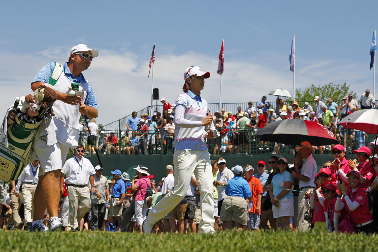 Na Yeon Choi, right, of South Korea, walks after hitting her tee shot on the first hole during the final round of the U.S. Women's Open golf tournament on Sunday, July 8, 2012, in Kohler, Wis. (AP Photo/Jeffrey Phelps)