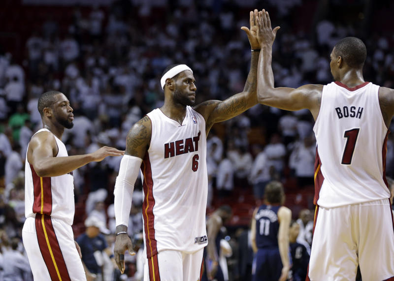 In this April 23, 2014 file photo, Miami Heat's LeBron James (6) high-fives Chris Bosh (1) after the Heat defeated the Charlotte Bobcats 101-97 in Game 2 of an opening-round NBA basketball playoff series in Miami. At left is Dwyane Wade. A person familiar with the situation tells The Associated Press that James has decided to opt out of the final two years of his contract with the Heat and become a free agent on July 1. Opting out does not mean James has decided to leave the Heat, said the person, who spoke on condition of anonymity because neither the four-time NBA MVP nor the team had made any public announcement
