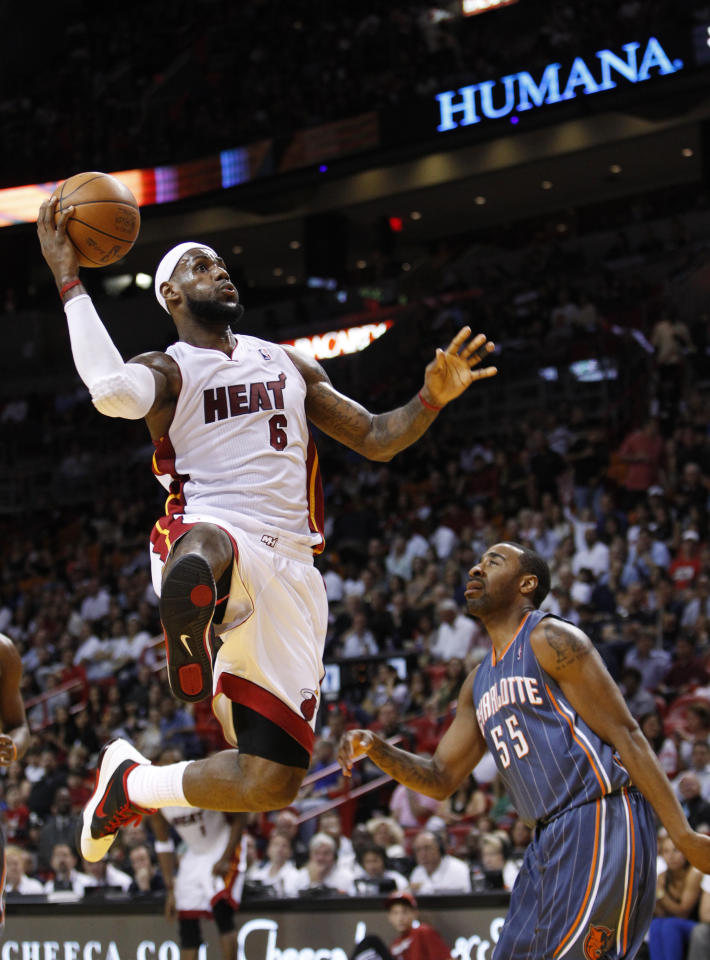 Miami Heat forward LeBron James goes up for a shot against Charlotte Bobcats forward Reggie Williams (55) during the first half of an NBA basketball game, Friday, April 13, 2012 in Miami. (AP Photo/Wilfredo Lee)