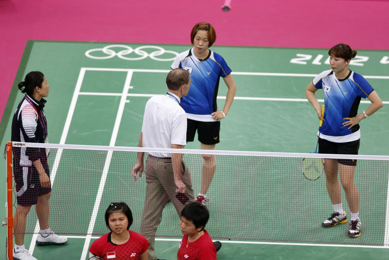 """Tournament referee Torsten Berg (3rd R) speaks to players from South Korea (in blue) and Indonesia (in red) during their women's doubles group play stage Group C badminton match during the London 2012 Olympic Games at the Wembley Arena July 31, 2012. The four players from the match are among eight female players charged by the World Badminton Federation with misconduct on Wednesday after four Olympic doubles teams had attempted to """"throw"""" matches to secure a more favourable draw later in the tournament. The players involved in Tuesday's matches were China's world champions Wang Xiaoli and Yu Yang, Indonesia's Greysia Polii (bottom L) and Meiliana Jauhari (bottom R) and two South Korean pairs - Jung Kyung-eun and Kim Ha-na, and Ha Jung-eun (top R) and Kim Min Jung (top L). Picture taken July 31, 2012. REUTERS/Bazuki Muhammad (BRITAIN  - Tags: SPORT BADMINTON SPORT OLYMPICS)"""