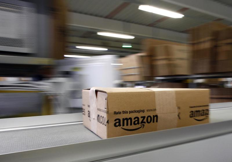 A parcel moves on the conveyor belt at Amazon's logistics centre in Graben near Augsburg in this file photo from December 16, 2013. Amazon.com Inc reported a $239 million fourth-quarter net profit January 30, 2014, helped by strong U.S. sales during the most competitive holiday season since the recession. REUTERS/Michaela Rehle/Files (GERMANY - Tags: BUSINESS EMPLOYMENT)
