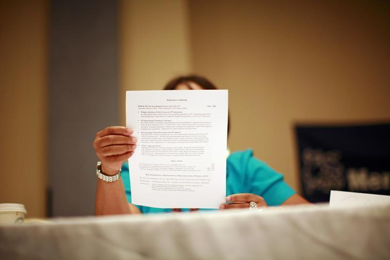 A woman looks over a resume during a job fair in New York