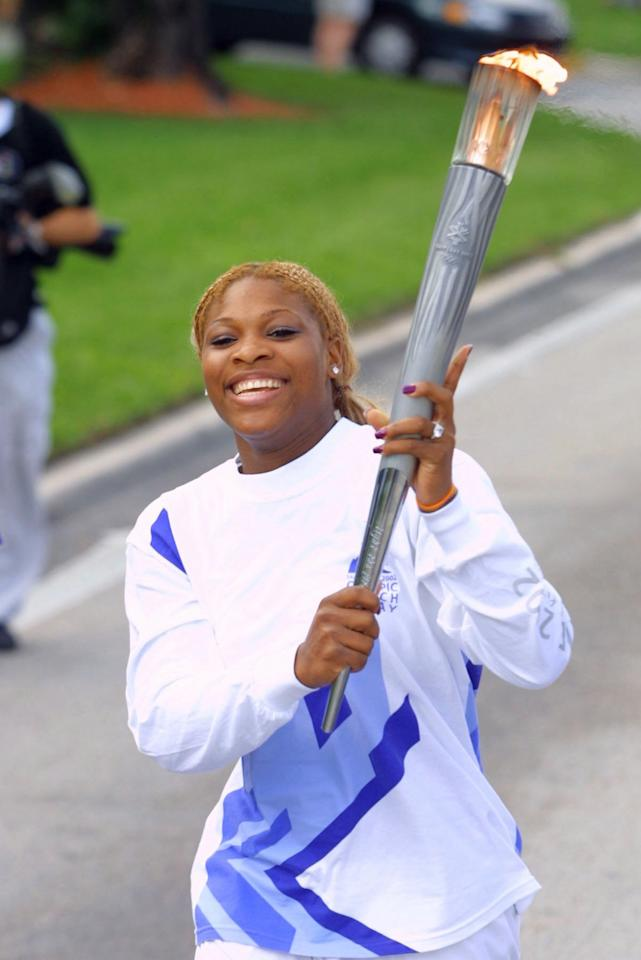 Tennis superstar Serena Williams carries the Olympic flame as a  torchbearer during the 2002  Olympic Torch Relay Saturday, Dec. 8, 2001, in Ft. Laurderdale, Fla. The torch makes its journey to Salt Lake City traveling more than 13,500 miles across the United States in 65 days carried by about 11,500 torchbearers  (AP Photo/Todd Warshaw, Pool)