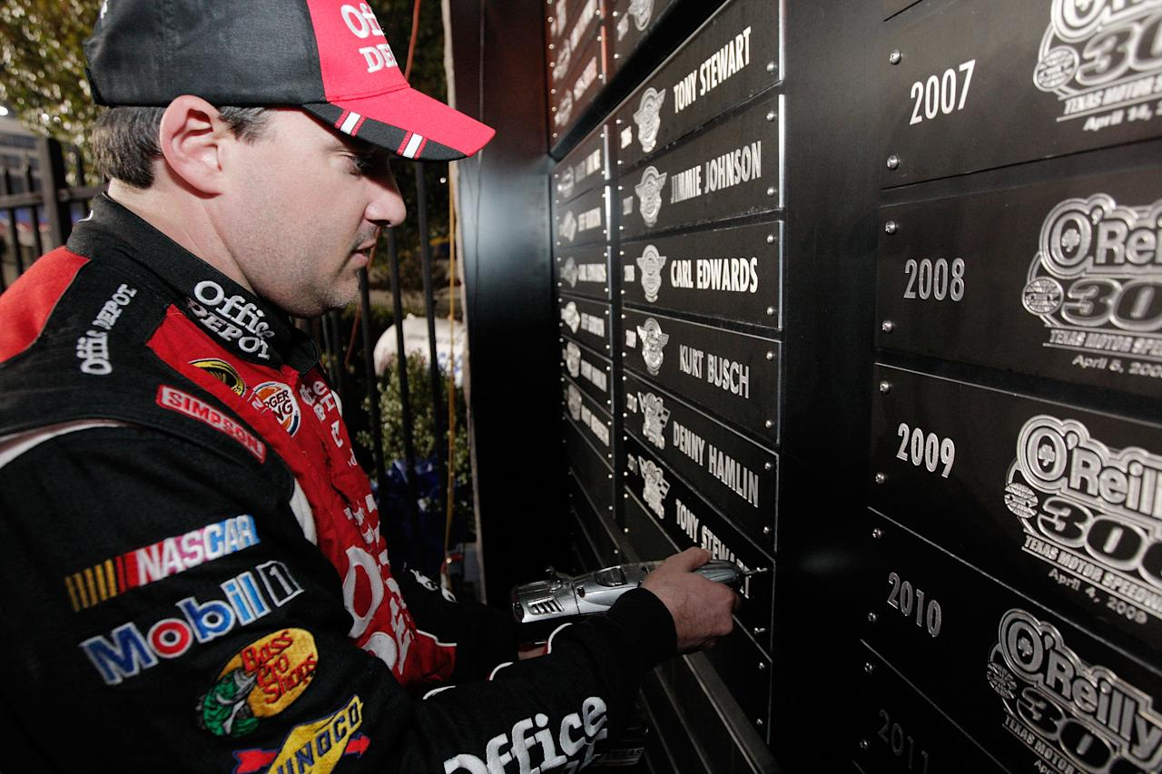 FORT WORTH, TX - NOVEMBER 06:  Tony Stewart, driver of the #14 Office Depot/Mobil 1 Chevrolet, screws his name plate in to the Wall of Champions in Victory Lane after winning the NASCAR Sprint Cup Series AAA Texas 500 at Texas Motor Speedway on November 6, 2011 in Fort Worth, Texas.  (Photo by Brandon Wade/Getty Images for NASCAR)