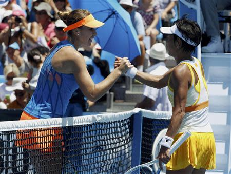 Bencic of Switzerland clasps hands with Date-Krumm of Japan at the net after defeating her in their women's singles match at the Australian Open 2014 tennis tournament in Melbourne