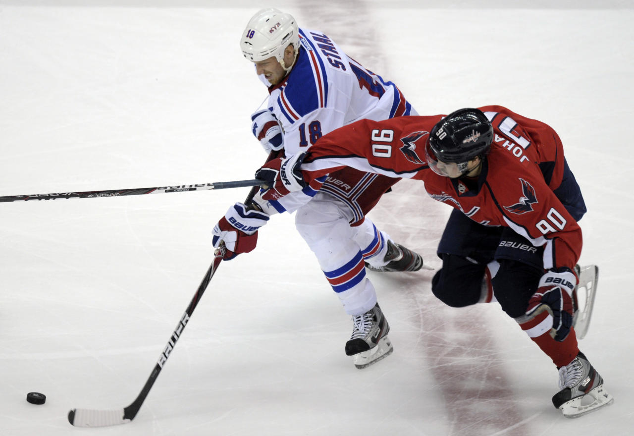 Washington Capitals center Marcus Johansson (90) and New York Rangers defenseman Marc Staal (18) vie for the puck in the first period of Game 6 of a second-round NHL hockey Stanley Cup playoff series, in Washington on Wednesday, May 9, 2012. (AP Photo/Susan Walsh)