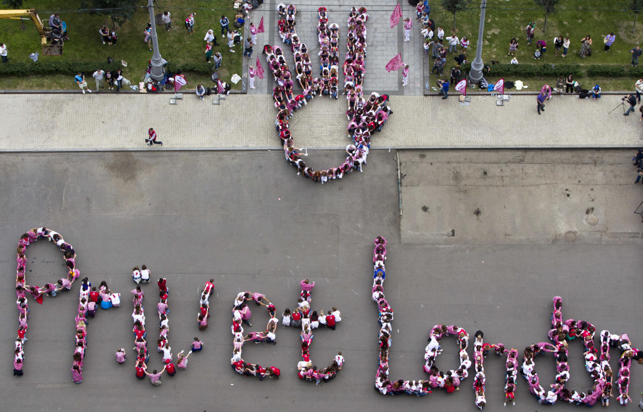 Young Russian athletes present new Russian Olympic national team uniform and form letters reading Hi London, in Moscow, Russia, Thursday, June 28, 2012. (AP Photo/Misha Japaridze)