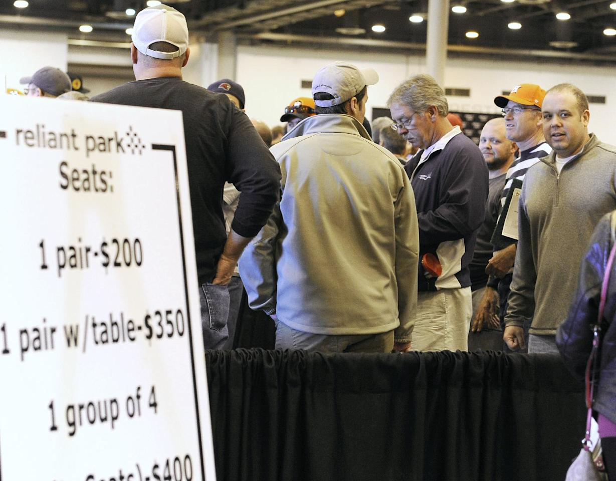 People line up to buy stadium seats at a sale and auction of Houston Astrodome furniture, appliances, Astroturf and staff uniforms on Saturday, Nov. 2, 2013, at the Reliant Center in Houston. The Astrodome was the world's first multipurpose domed stadium and was once home to the Astros and the Oilers. The stadium has been closed to all events since 2009. (AP Photo/Pat Sullivan)