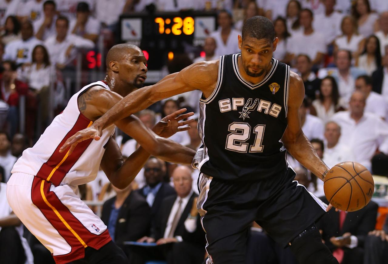 MIAMI, FL - JUNE 18: Tim Duncan #21 of the San Antonio Spurs drives on Chris Bosh #1 of the Miami Heat in the first quarter during Game Six of the 2013 NBA Finals at AmericanAirlines Arena on June 18, 2013 in Miami, Florida. NOTE TO USER: User expressly acknowledges and agrees that, by downloading and or using this photograph, User is consenting to the terms and conditions of the Getty Images License Agreement. (Photo by Mike Ehrmann/Getty Images)