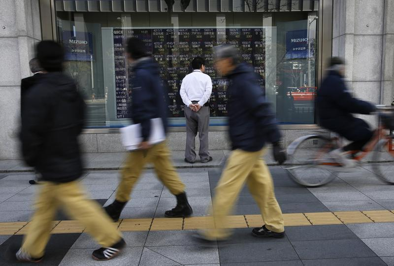 A man looks at a stock quotation board as passers-by walk past outside a brokerage in Tokyo