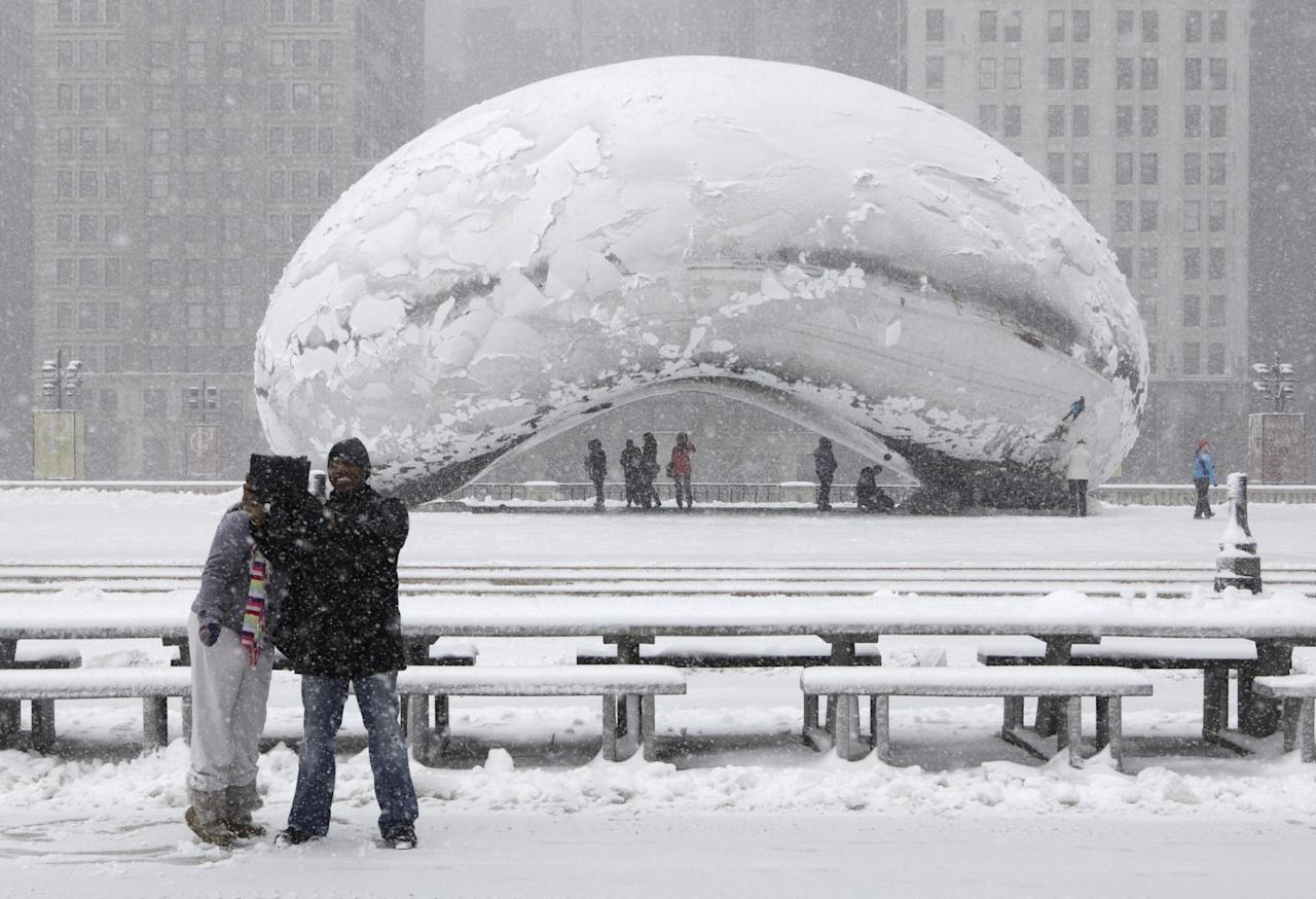 Onlookers take pictures in front of Cloud Gate, a public sculpture by Indian-born British artist Anish Kapoor, as they walk around the Millennium Park as a snow storm passes through the region Tuesday, March 5, 2013, in Chicago. Chicago was hit Tuesday by a storm expected to dump as much as 10 inches of snow in the area before the end of the day — the most since the 2011 blizzard and its more than 20 inches of snow. (AP Photo/Kiichiro Sato)