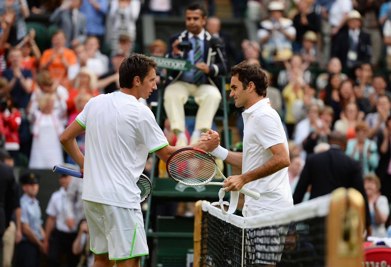 LONDON, ENGLAND - JUNE 26: Sergiy Stakhovsky of Ukraine shakes hands at the net with Roger Federer of Switzerland after their Gentlemen's Singles second round match on day three of the Wimbledon Lawn Tennis Championships at the All England Lawn Tennis and Croquet Club on June 26, 2013 in London, England. (Photo by Mike Hewitt/Getty Images)