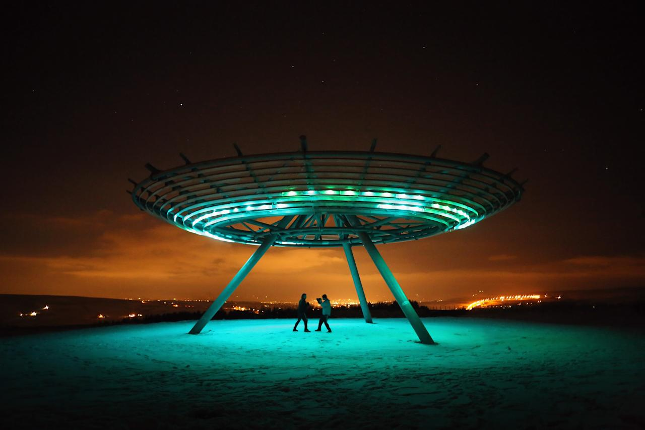 RAWTENSTALL, ENGLAND - JANUARY 15:  Two boxers train under the illumination of the Haslingden Halo Panopticon on January 15, 2013 in Rawtenstall, England. The installation designed by John Kennedy of LandLab sits on a hill called Top o' Slate, a reclaimed landfill site in East Lancashire and has become a major landmark since opening in 2011. 'Halo' is the centrepiece of panopticons art projects, led by the REMADE in Lancashire programme, Groundwork and Rossendale Council, which has reclaimed and returned to public use 33 hectares of land.  (Photo by Christopher Furlong/Getty Images)