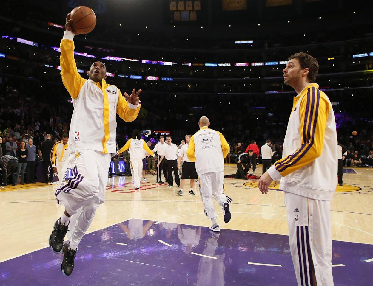 Los Angeles Lakers' Kobe Bryant makes his first layup in warm-ups as Pau Gasol, right, of Spain, looks on before the NBA basketball game against the Toronto Raptors  in Los Angeles, Sunday, Dec. 8, 2013. Bryant is expected to make his long-awaited return from a torn left Achilles tendon injury from April 12th. (AP Photo/Danny Moloshok)
