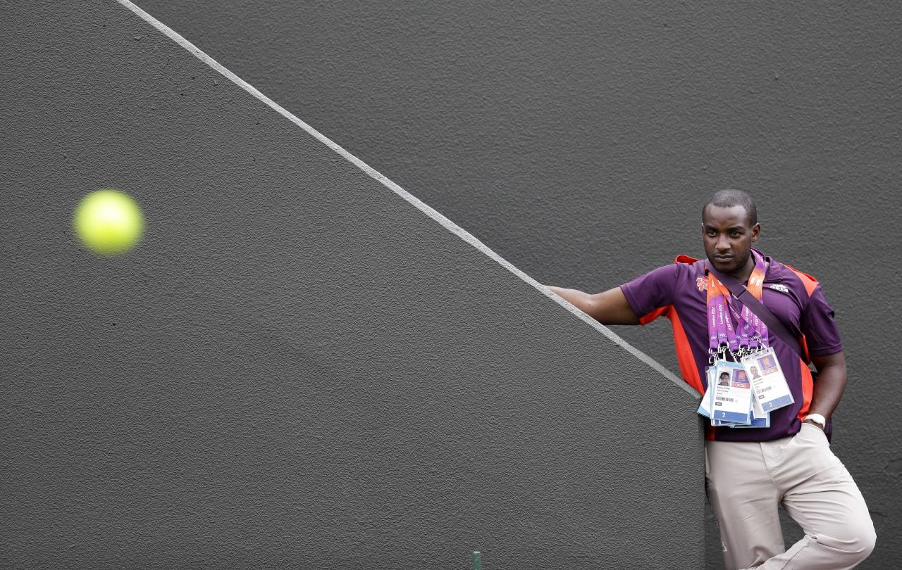 Leon Lee, a supervisor for the ball boys and ball girls, watches a tennis match at the All England Lawn Tennis Club at Wimbledon, in London, at the 2012 Summer Olympics, Saturday, July 28, 2012. (AP Photo/Mark Humphrey)