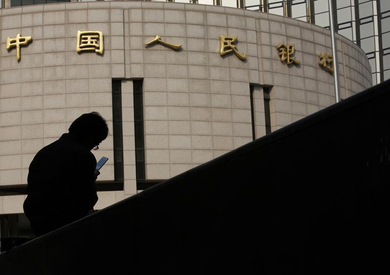 Man sits in front of the headquarters of the People's Bank of China, the central bank, in Beijing