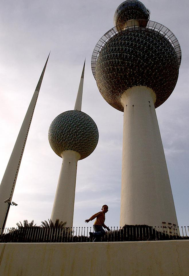 A boy runs along a wall in front of the Kuwaiti towers in the late afternoon 04 April 2003, sixteen days after US-led coalition troops staged a major attack on Iraq in an effort to unseat the Saddam Hussein regime in Bagdad. Life in Kuwait is slowly returning back to normal following a series of Iraqi missile attacks against the Gulf emirate thoughout the first two weeks of the war.  AFP PHOTO/Roberto SCHMIDT
