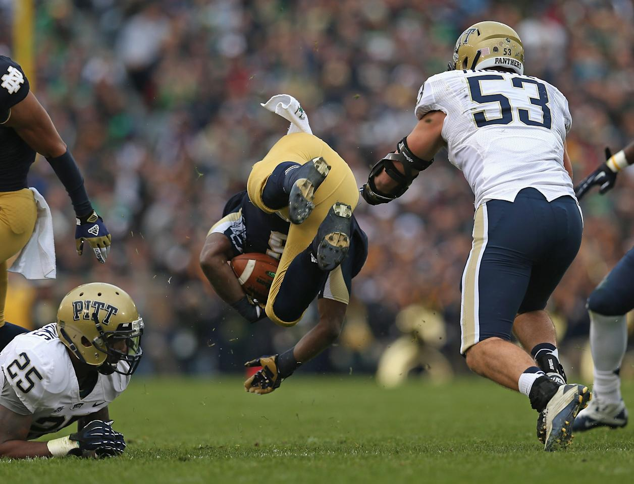 SOUTH BEND, IN - NOVEMBER 03: Theo Riddick #6 of the Notre Dame Fighting Irish flips in the air between Jason Hendricks #25 and Joe Trebitz #53 of the Pittsburgh Panthers at Notre Dame Stadium on November 3, 2012 in South Bend, Indiana. (Photo by Jonathan Daniel/Getty Images)
