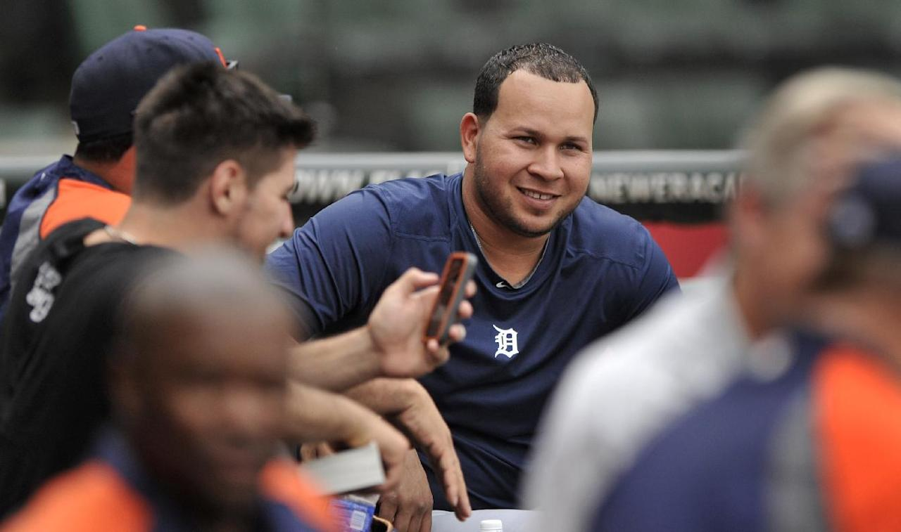 Suspended Detroit Tigers shortstop Jhonny Peralta jokes with teammates in the dugout after working out with theteam before an MLB baseball game against the Chicago White Sox in Chicago, Wednesday, Sept. 11, 2013. Peralta accepted a 50-game suspension from Major League Baseball on Aug. 5 as part of its investigation into Biogenesis of America, a Florida anti-aging clinic accused of distributing banned performance-enhancing drugs. (AP Photo/Paul Beaty)