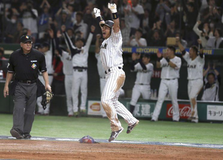 Japan's Nobuhiro Matsuda celebrates at home after scoring on Seiichi Uchikawa's sacrifice fly against Cuba in the eighth inning of their second round game at the World Baseball Classic at Tokyo Dome in Tokyo Tuesday