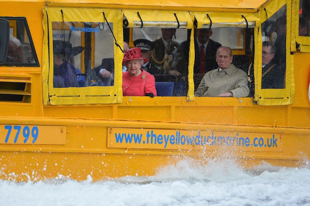 LIVERPOOL, ENGLAND - MAY 17:  Queen Elizabeth II and Prince Philip, Duke of Edinburgh take a ride on the Yellow Duck and amphibious vehicle during a visit to Merseyside Maritime Museum on May 17, 2012 in Liverpool, England. The Queen is visiting many parts of Britain as she celebrates her Diamond Jubilee culminating with a four-day public holiday on June 2-5, including a pageant of 1,000 boats on the River Thames.  (Photo by Jeff J Mitchell/Getty Images)