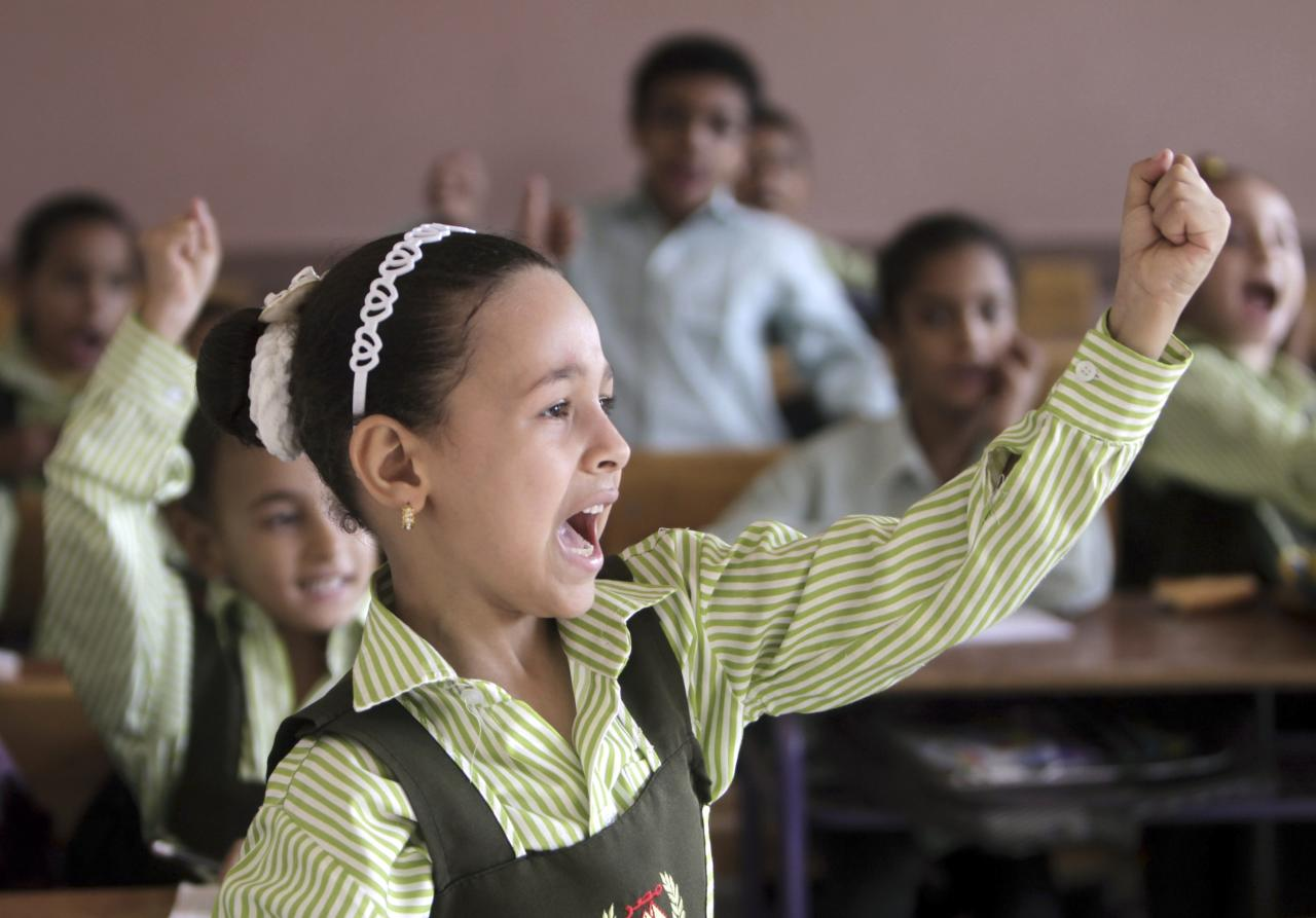 Students raise their hands in class on the first day of their new school year at a government school in Giza, south of Cairo September 22, 2013. Students resumed their studies at the beginning of the new academic year this weekend amid parental concerns of a possible lack of security after the summer vacation ends. REUTERS/Mohamed Abd El Ghany (EGYPT - Tags: POLITICS EDUCATION)