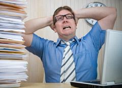 Man with hands on his head behind a mound of paperwork