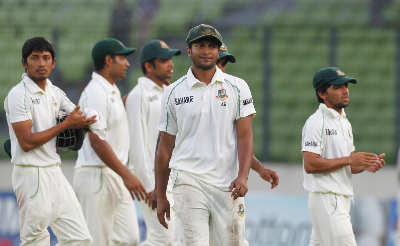 Bangladesh's Shakib Al Hasan (C) comes off the field with other players after the end of the third day of second test cricket match against New Zealand in Dhaka October 23, 2013. REUTERS/Andrew Biraj (BANGLADESH - Tags: SPORT CRICKET)