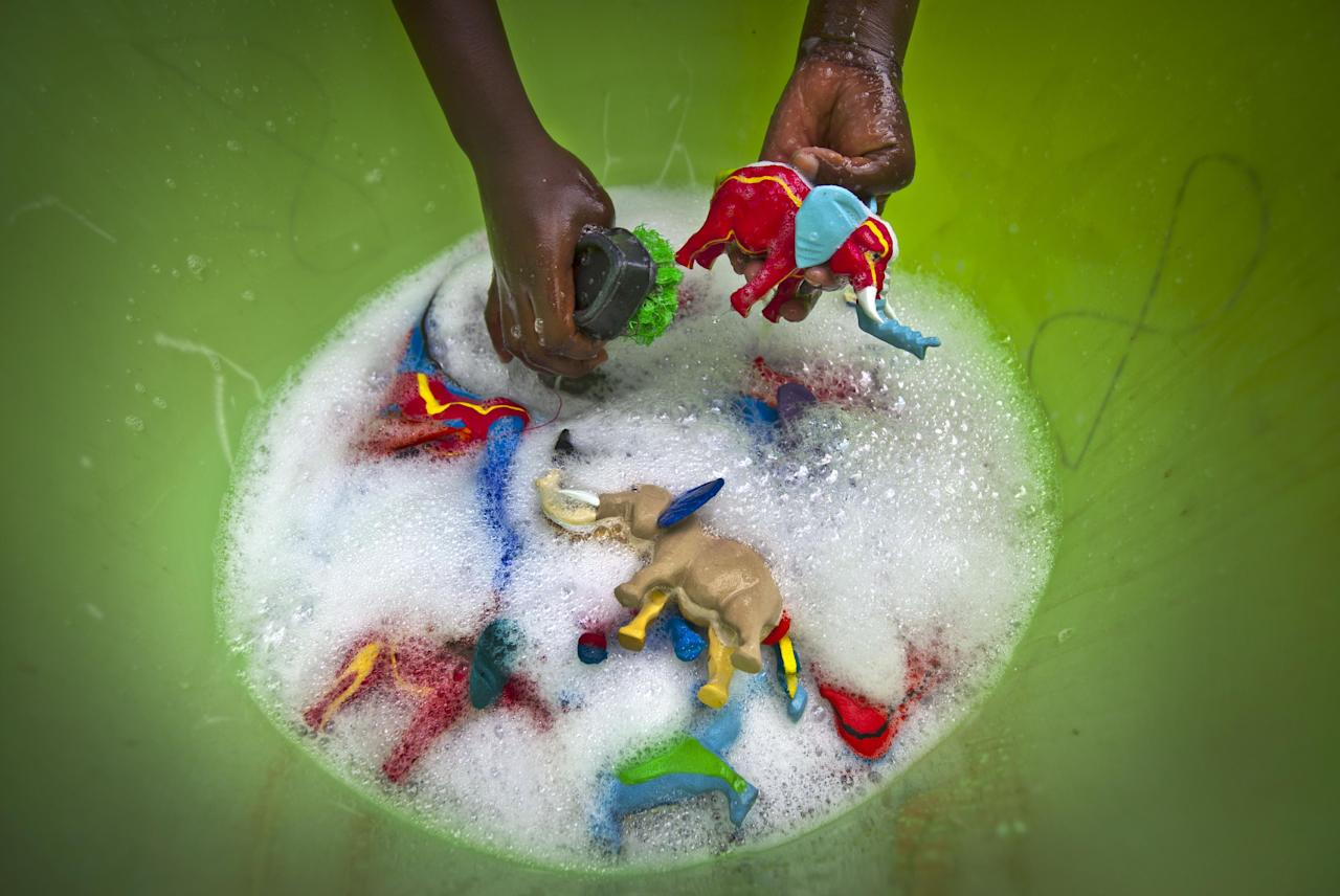 In this photo taken Monday, April 29, 2013, a female worker washes some finished toy animals made from pieces of discarded flip-flops, in a bucket at the Ocean Sole flip-flop recycling company in Nairobi, Kenya. The company is cleaning the East African country's beaches of used, washed-up flip-flops and the dirty pieces of rubber that were once cruising the Indian Ocean's currents are now being turned into colorful handmade giraffes, elephants and other toy animals. (AP Photo/Ben Curtis)