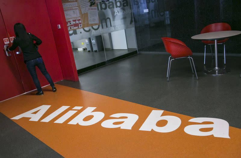 A woman stands next to a door inside the headquarters of Alibaba in Hangzhou