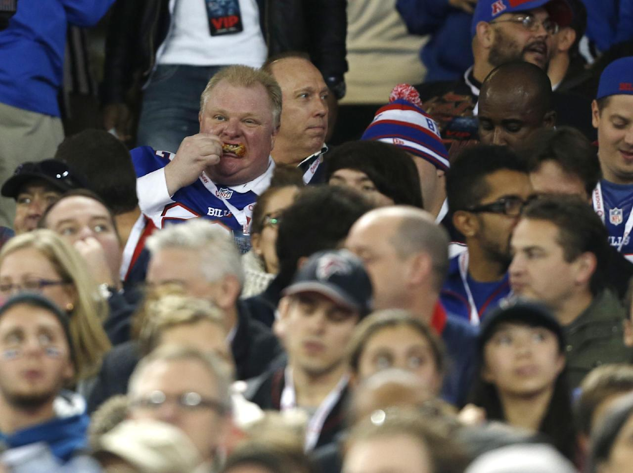 Toronto Mayor Rob Ford eats during the first half of an NFL football game between the Atlanta Falcons and the Buffalo Bills on Sunday, Dec. 1, 2013, in Toronto. (AP Photo/Gary Wiepert)