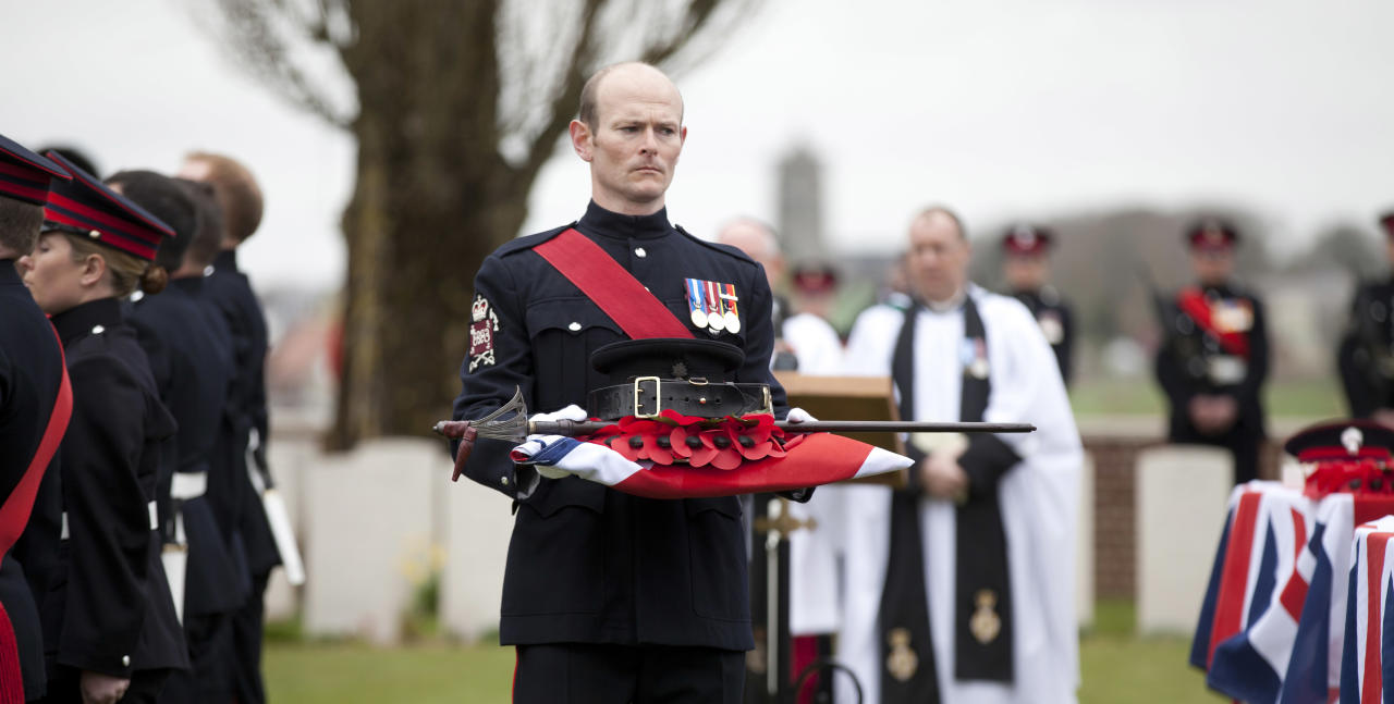 A poppy wreath and sword of Lieutenant John Harold Pritchard are carried by a soldier during a ceremony at the H.A.C. cemetery in Ecoust-St-Mein, France on Tuesday, April 23, 2013. Almost 100 years after they were killed in action, Lieutenant John Harold Pritchard and Private Christopher Douglas Elphick were re-interred with full military honors in a private ceremony. . Lieutenant Pritchard was killed in action on May 15, 1917 during an enemy attack near Bullecourt, France and his remains were found in a field near the site in 2009. His body was eventually identified by a silver bracelet with his name engraved on it. (AP Photo/Virginia Mayo)