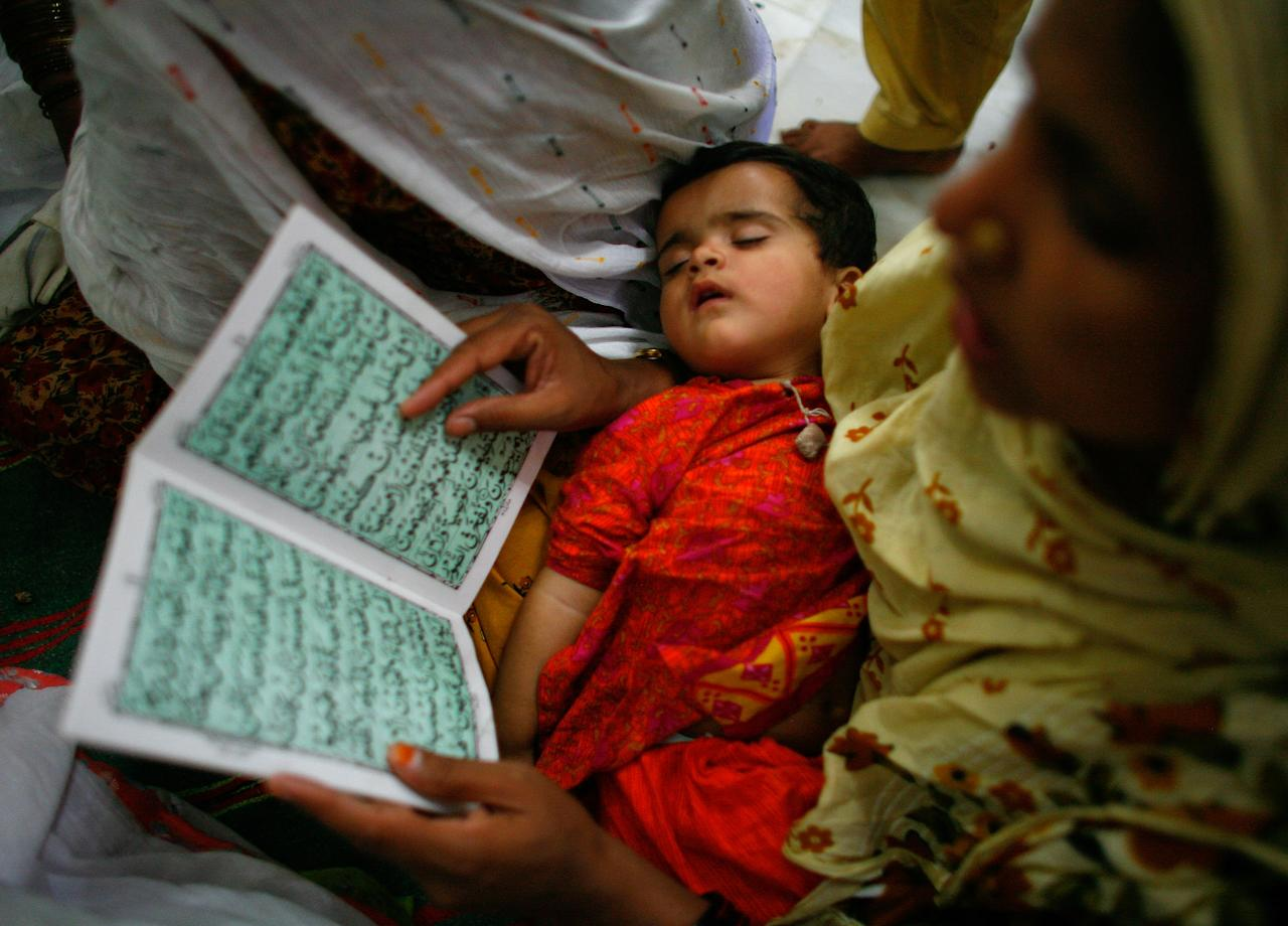 ISLAMABAD-PAKISTAN-MAY 31: A Pakistani woman prays next to the shrine of Bari Imam Abdul Latif Kazmi as her baby sleeps, paying homage during the annual Bari Imam festival in Islamabad, May 31, 2007. Thousands of Pakistani pilgrims turn out every year to honor the 17th century sufi, considered the patron saint of Islamabad.  (Photo by Paula Bronstein /Getty Images)