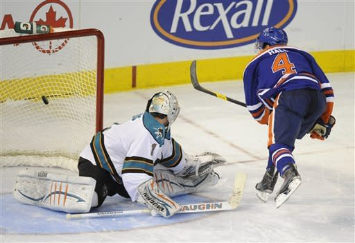 Edmonton Oilers' Taylor Hall, right, scores the winning shoot out goal on San Jose Sharks goalie Thomas Greiss during NHL hockey action in Edmonton on Monday, Jan. 23, 2012. (AP Photo/The Canadian Press, John Ulan)