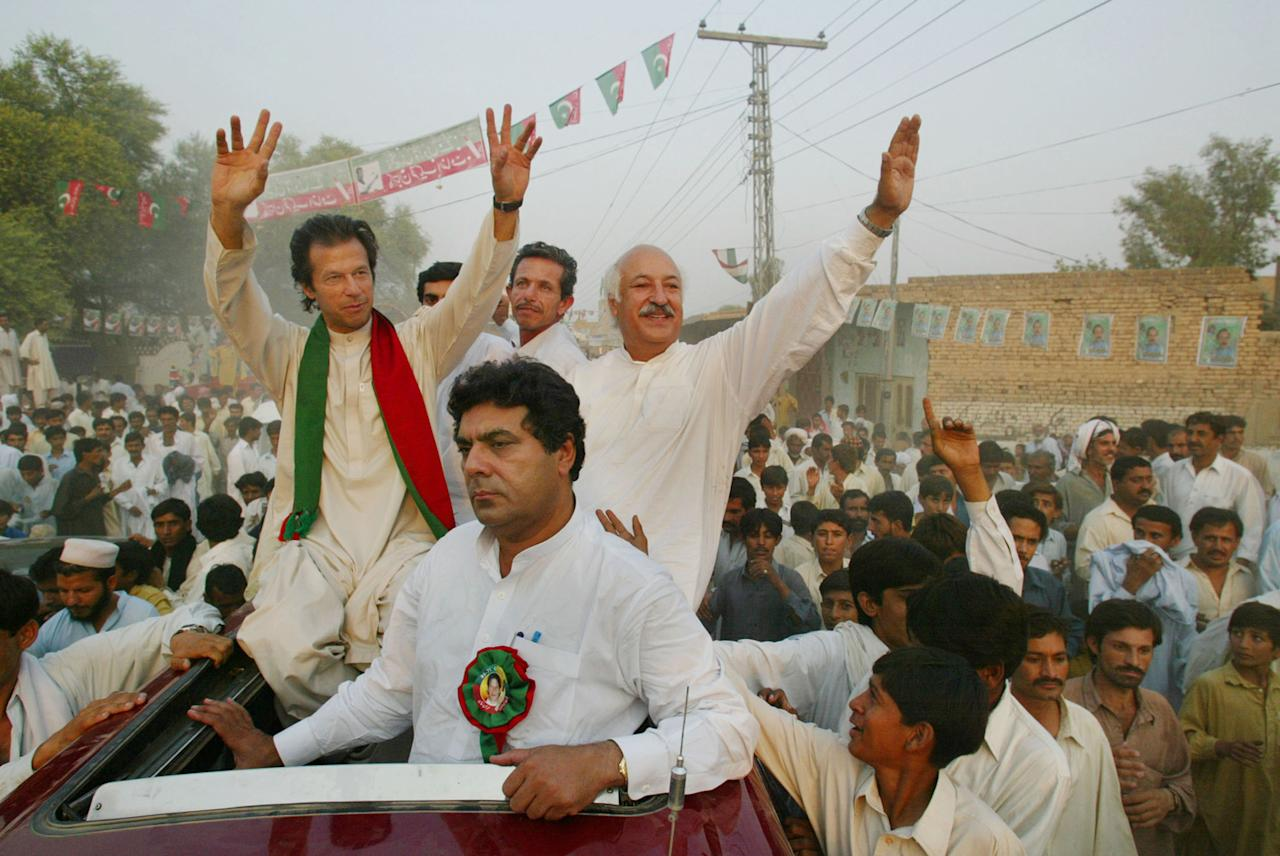 SHADI KHAL, PAKISTAN - OCTOBER 8:  Imran Khan (L), cricket captain turned politician and chairman of the Dhirir Tehrik-e-Insaf political party, waves to supporters during a rally October 8, 2002 in Shadi Khal, Pakistan. Thursday's vote is the first election to be held since President Pervez Musharraf seized power three years ago.  (Photo by Paula Bronstein/Getty Images)