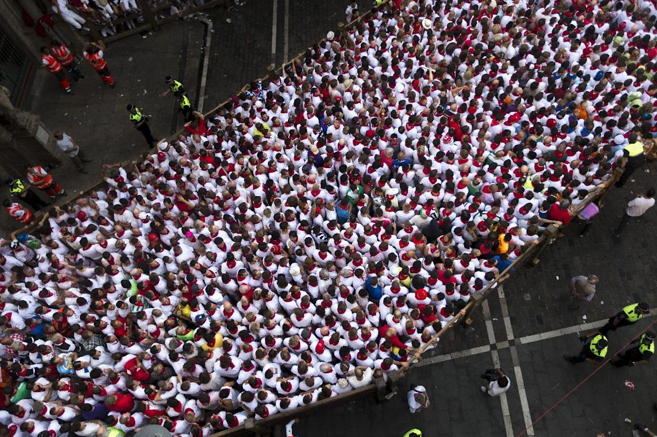 Revelers wait for the running of the bulls during the San Fermin fiestas, Monday, July 8, 2013 in Pamplona, Spain. Revelers from around the world come to San Fermin festival to take part in the party and in some of the eight days of the running of the bulls glorified by Ernest Hemingway's 1926 novel 'The Sun Also Rises'. (AP Photo/Daniel Ochoa de Olza)