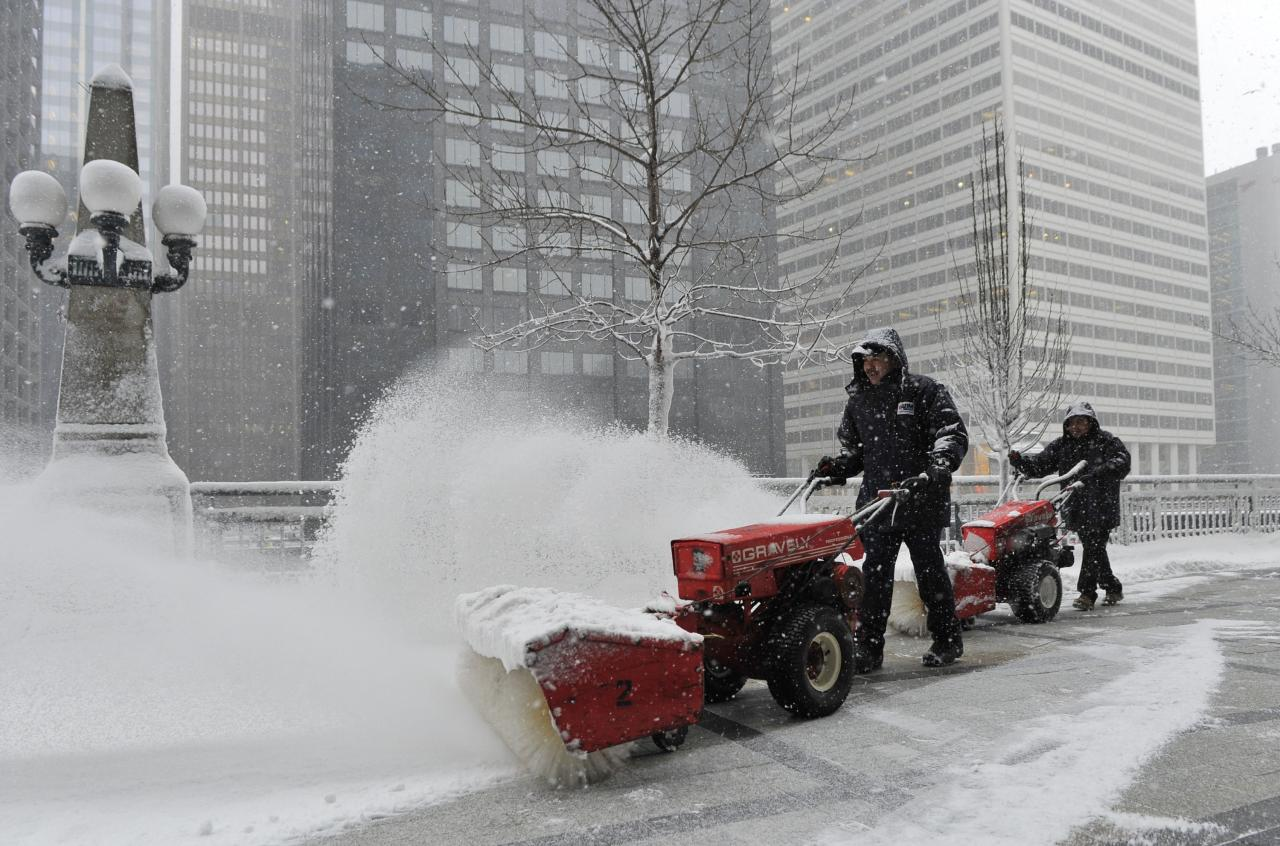 CHICAGO, IL - MARCH 5:  Arturo Garcia (L) and Ricardo Perez clear snow from Riverside Plaza on March 5, 2013 in Chicago, Illinois. The worst winter storm of the season is expected to dump 7-10 inches of snow on the Chicago area with the worst expected for the evening commute.  (Photo by Brian Kersey/Getty Images)