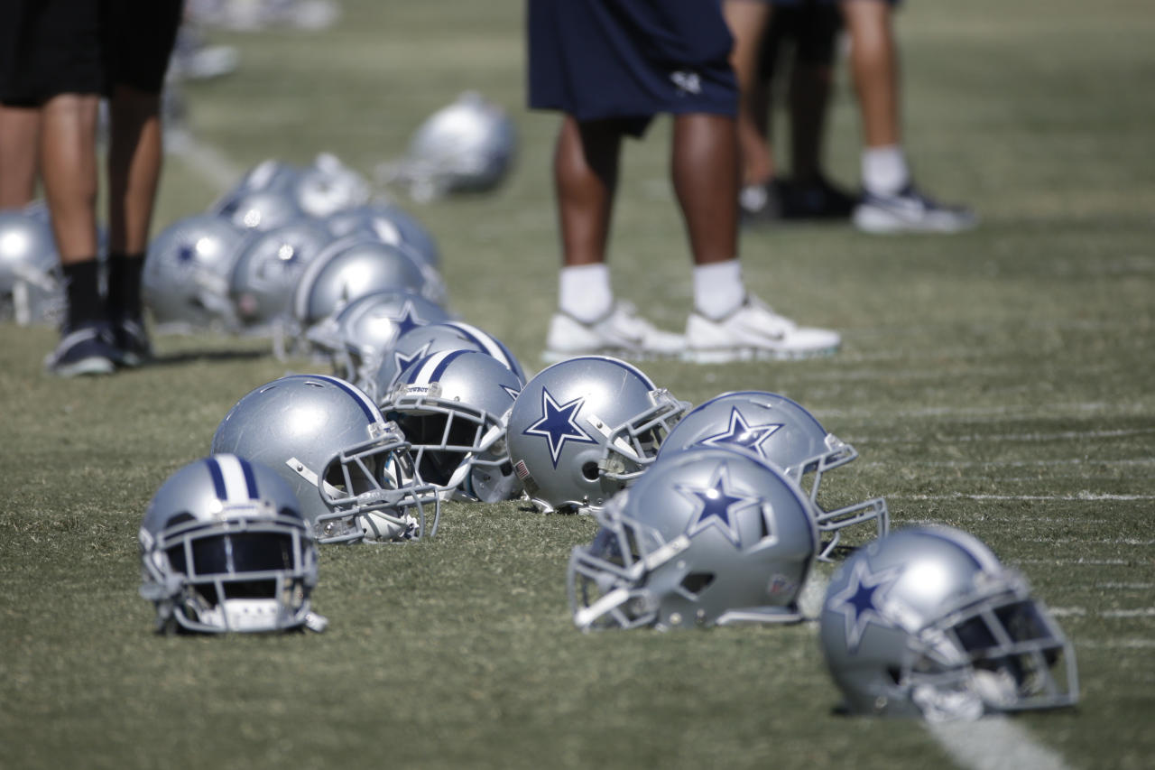 Some helmets for the Dallas Cowboys are seen on the field in a joint football practice with the Oakland Raiders on Tuesday, Aug. 12, 2014, in Oxnard, Calif. (AP Photo/Jae C. Hong)