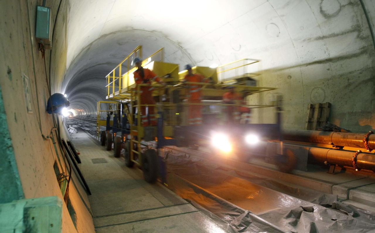 Workers drive on a special vehicle during the installation of the railway tracks in the NEAT Gotthard Base tunnel near Erstfeld May 7, 2012. Crossing the Alps, the world's longest train tunnel should become operational at the end of 2016. The project consists of two parallel single track tunnels, each of a length of 57 km (35 miles)  REUTERS/Arnd Wiegmann   (SWITZERLAND - Tags: BUSINESS CONSTRUCTION EMPLOYMENT TRAVEL)