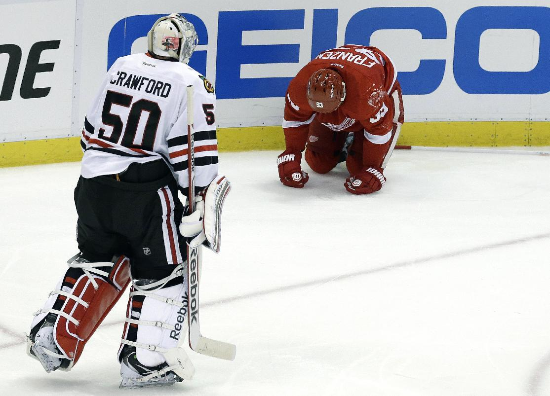 Chicago Blackhawks goalie Corey Crawford (50) skates towards Detroit Red Wings left wing Johan Franzen (93), of Sweden, after he hit the boards during the third period of an NHL hockey Stanley Cup playoffs Western Conference semifinal game in Detroit, Monday, May 20, 2013. (AP Photo/Paul Sancya)