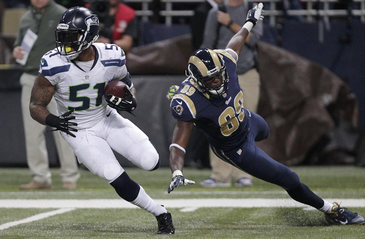 Seattle Seahawks outside linebacker Bruce Irvin (51) runs against St. Louis Rams tight end Jared Cook (89) after intercepting the pass during the first half of an NFL football game, Monday, Oct. 28, 2013, in St. Louis. (AP Photo/Tom Gannam)