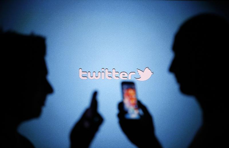 Men are silhouetted against a video screen with a Twitter logo as they pose with Samsung S3 and S4 smartphones in this photo illustration taken in the central Bosnian town of Zenica