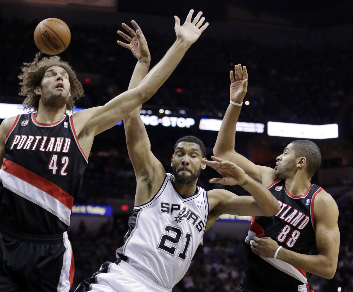 Portland Trail Blazers' Robin Lopez (42) and Nicolas Batum (88) battle with San Antonio Spurs' Tim Duncan (21) for a rebound during the first half of Game 1 of a Western Conference semifinal NBA basketball playoff series, Tuesday, May 6, 2014, in San Antonio. (AP Photo/Eric Gay)