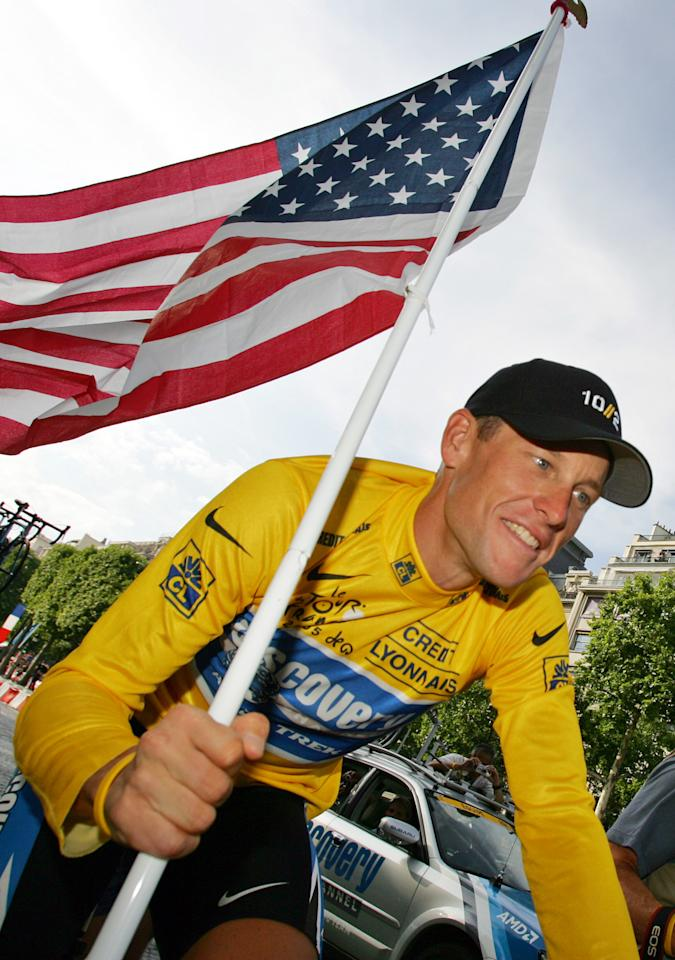 FILE - In this July 24, 2005 file photo, Lance Armstrong, of Austin, Texas, carries the United States flag and wears a jersey with Nike logos during a victory parade on the Champs Elysees avenue in Paris, after winning his seventh straight Tour de France cycling race. Nike Inc. is cutting ties with the Livestrong cancer charity founded by Armstrong. The move by the sports company is the latest fallout in the doping scandal surrounding the former cyclist, who now admits he used performance-enhancing drugs to win the Tour de France seven times. (AP Photo/Peter Dejong, File)