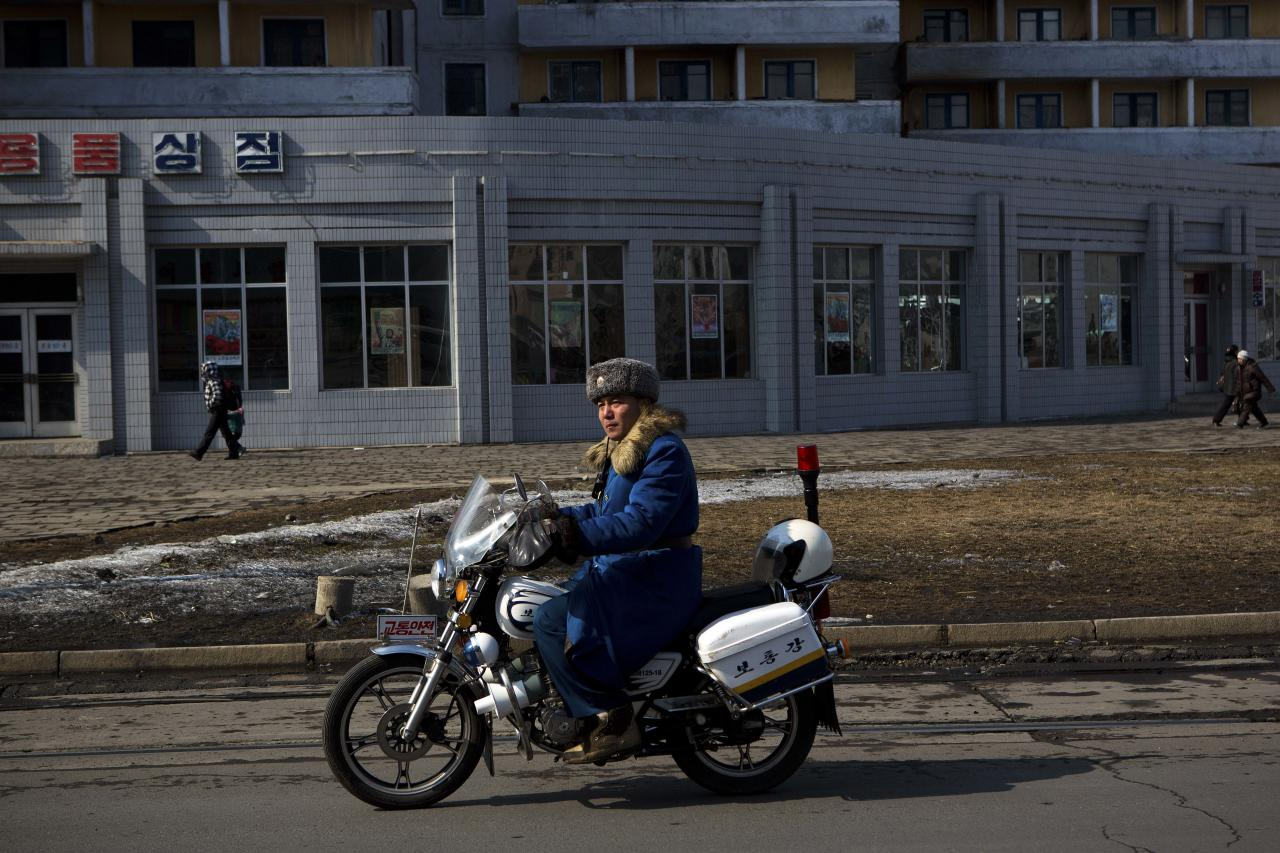 A North Korean traffic policeman on a motorcycle patrols a street in central Pyongyang, North Korea on Friday, Feb. 22, 2013. (AP Photo/David Guttenfelder)